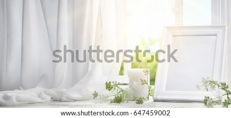 Picture frame near window with candle in the morning