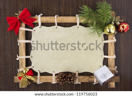 Picture frame with blank canvas space decorated with Christmas baubles, bell, ribbon, tree branch and cones on wooden board background - stock photo