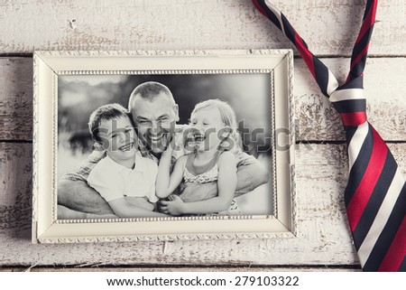 Picture frame with family photo and colorful tie laid on wooden backround.