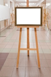 picture frame with white cut out canvas on easel in art gallery