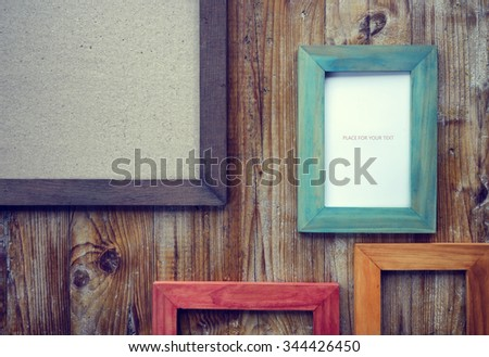 picture frames of different colors and wooden background