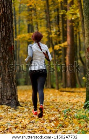Picture from back of young sporty brunette in running through forest