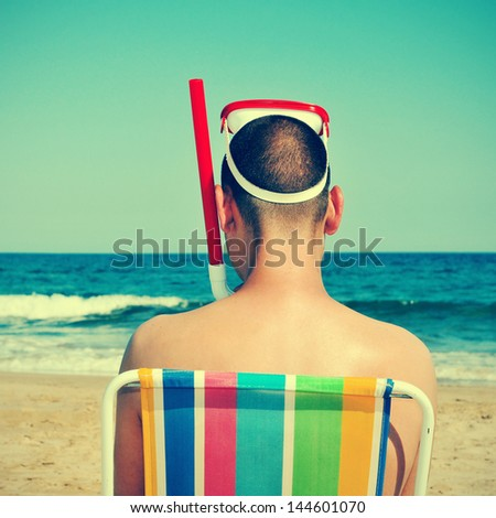 picture from the back of a man wearing a diving mask and a snorkel seated in a deckchair on the beach, with a retro effect