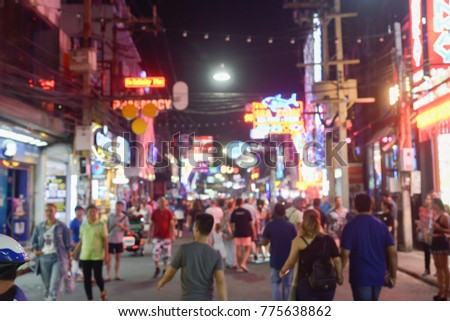 picture in motion blur of people crossing a city walking through the Walking Street in Pattaya,Thailand. Its a tourist attraction primarily for night life