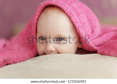 Picture of a baby lying under towel in bed
