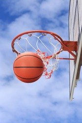 Picture of a basketball field goal with the blue sky clouds in background on an outdoor basketball court