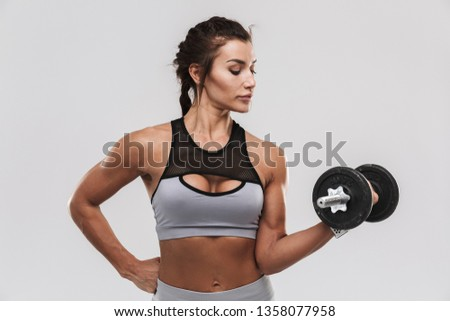 Picture of a beautiful young amazing strong sports fitness woman posing isolated over white wall background make exercises with dumbbell.