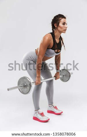 Picture of a beautiful young amazing strong sports fitness woman posing isolated over white wall background make exercises with barbell.