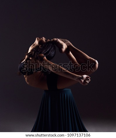 Picture of a beautiful young lady gymnast on stool on a dark background.