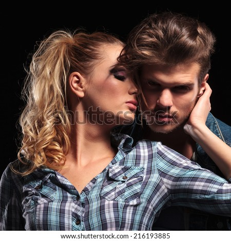 Picture of a blonde sexy woman looking away while holding her boyfriend close to her. The man is looking at the camera.