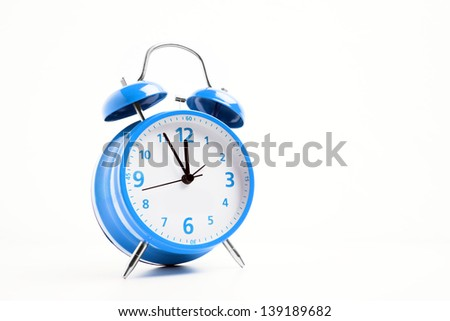 Picture of a blue retro alarm clock on a white background with the clock five to twelve