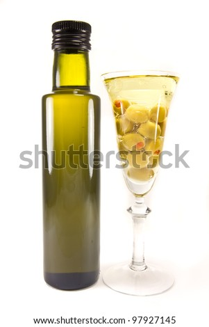 Picture of a bottle of olive oil and olives in a wine glass