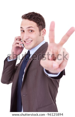 picture of a business man making victory sign while talking on the phone - stock photo