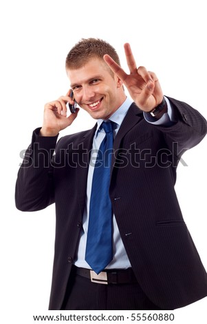 picture of a businessman making victory sign while talking on the phone - stock photo