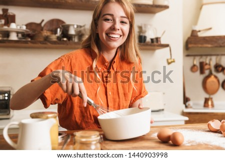 Picture of a cheerful young blonde girl chef cooking at the kitchen.