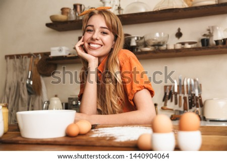 Picture of a cheery smiling young blonde girl chef cooking at the kitchen.