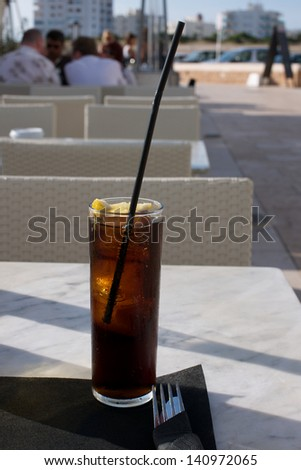 Picture of a cold cola on a table on an outside cafe