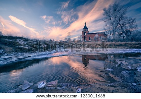 Picture of a cold November day with a frozen river and a church on the shore