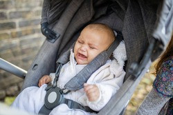 Picture of a distressed baby in gray clothing crying with eyes closed in a dark gray stroller on a sidewalk covered by leaves and next to a brick wall
