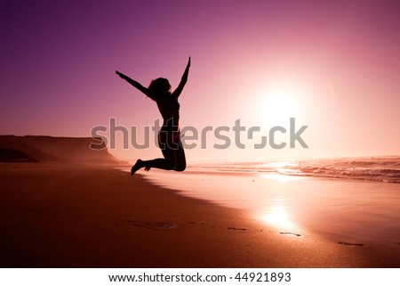 Picture of a female silhouette of a young girl jumping on the beach at the sunset