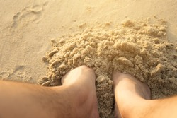 Picture of a foot buried in the sand at the beach.