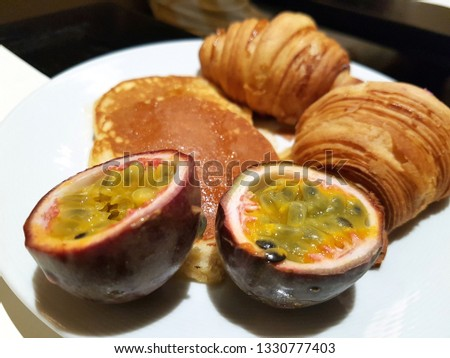 Picture of a fresh breakfast with passion fruit, pancakes and french pastries.