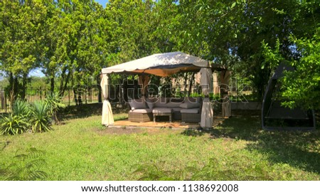 Picture of a gazebo with comfortable garden furniture.