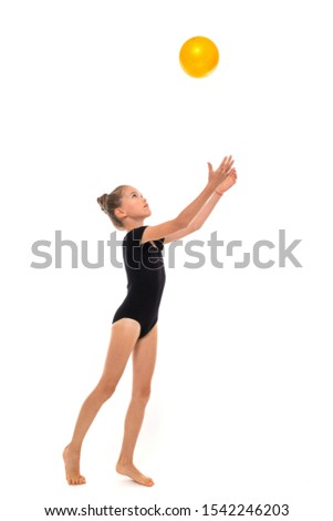 Picture of a gymnast girl in black trico full height throws the yellow ball up isolated on a white background
