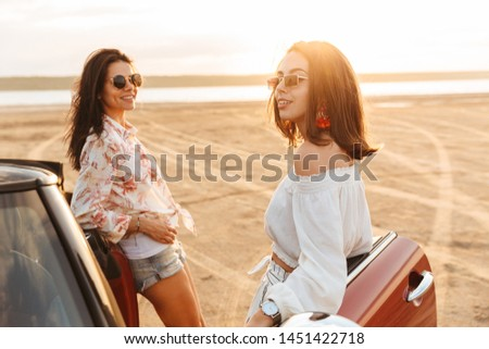 Picture of a happy cheery pretty young pretty women friends standing near car at the beach. #1451422718