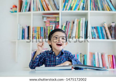 Picture of a happy little boy getting an idea while reading a book in the library with bookshelf background