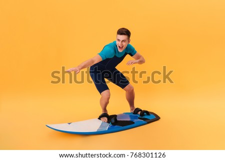 Picture of a Happy surfer in wetsuit using surfboard like on wave over yellow background