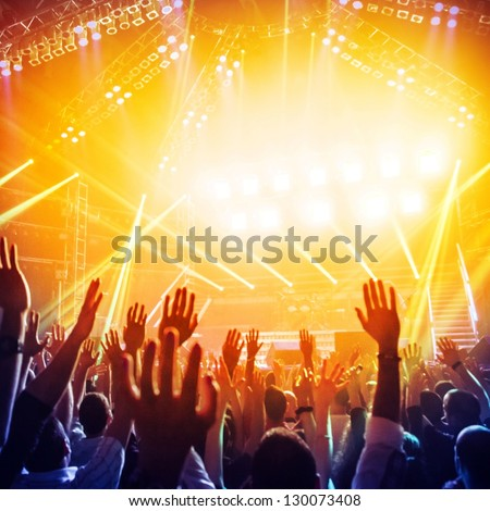 Picture of a lot of people enjoying night perfomance of famous dj large crowd of youth dancing with raised up hands on rock concert party in dance club bright yellow light from stage nightlife