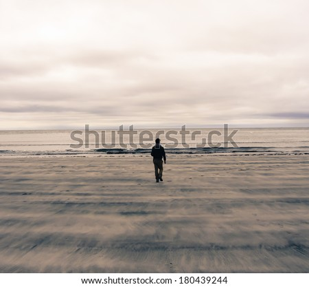 Picture of a man from behind walking on a beach in Scotland (UK). Watercolor Effect.