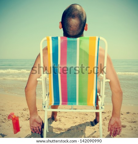 picture of a man sunbathing on a deckchair on the beach with a cocktail, with a retro effect