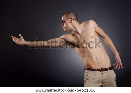 picture of a muscular man with sunglasses reaching out