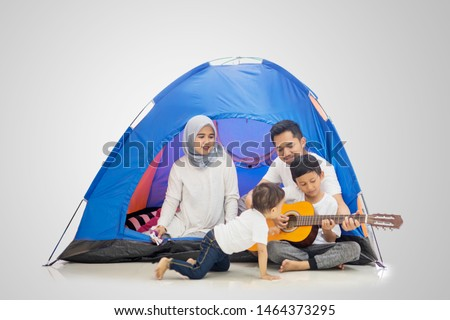 Picture of a Muslim family playing a guitar and singing in the tent while camping in the studio, isolated on white background