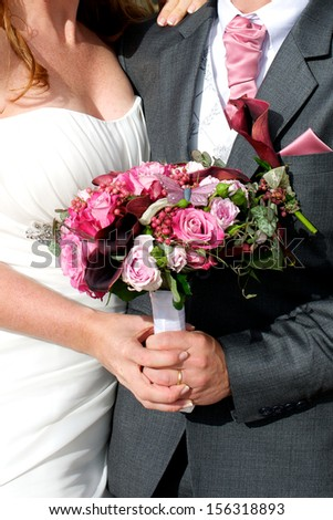 Picture of a newly wed couple holding the wedding bouquet between them