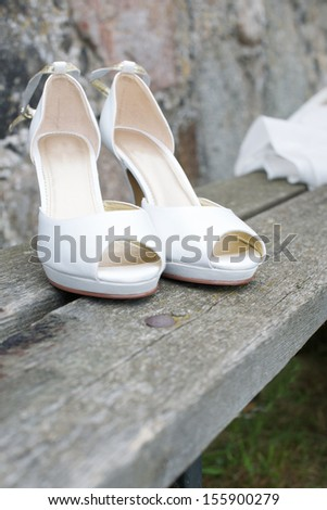 Picture of a pair of white wedding shoes on a bench