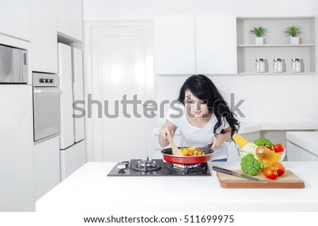 Picture of a pretty Asian woman cooking in the kitchen and sniff meal on the frying pan, shot at home