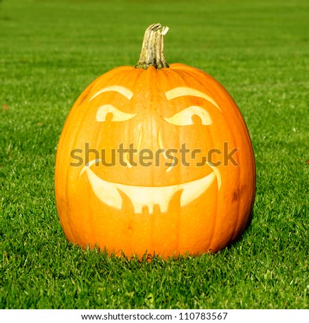 Picture of a pumpkin, with a scary face cut in the surface Standing on a lawn