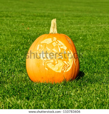 Picture of a pumpkin, with silhouette of a knight and horse cut in the surface Standing on a lawn