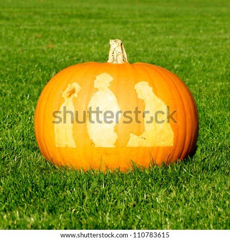Picture of a pumpkin, with silhouettes of people cut in the surface Standing on a lawn