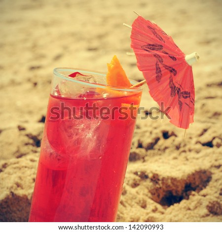 picture of a refreshing red cocktail with a red umbrella on the sand of a beach, with a retro effect
