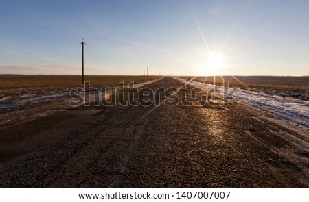 picture of a road in winter during sunset sunset. Rays of the sun in the frame