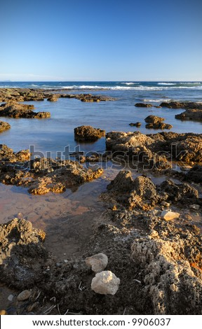 Picture of a rough rocky shoreline under a clear blue sky. Room for text at the top.
