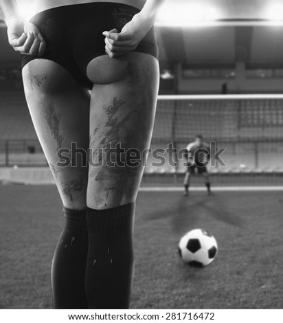 Picture of a sexy woman before a penalty kick. Goalkeeper in background.