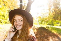 Picture of a smiling pleased cutie young student redhead girl in autumn park talking by mobile phone.