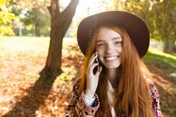Picture of a smiling pleased cutie young student redhead girl in autumn park using mobile phone talking.