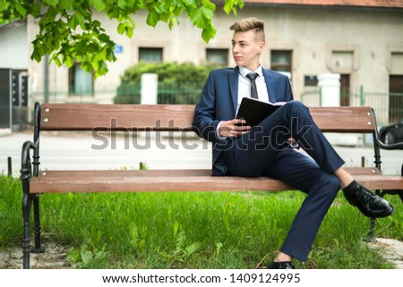 Picture of a teenage man in suit reading an interesting book in park
