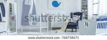 Picture of a whale hanging over a chest of drawers in a newborn room interior